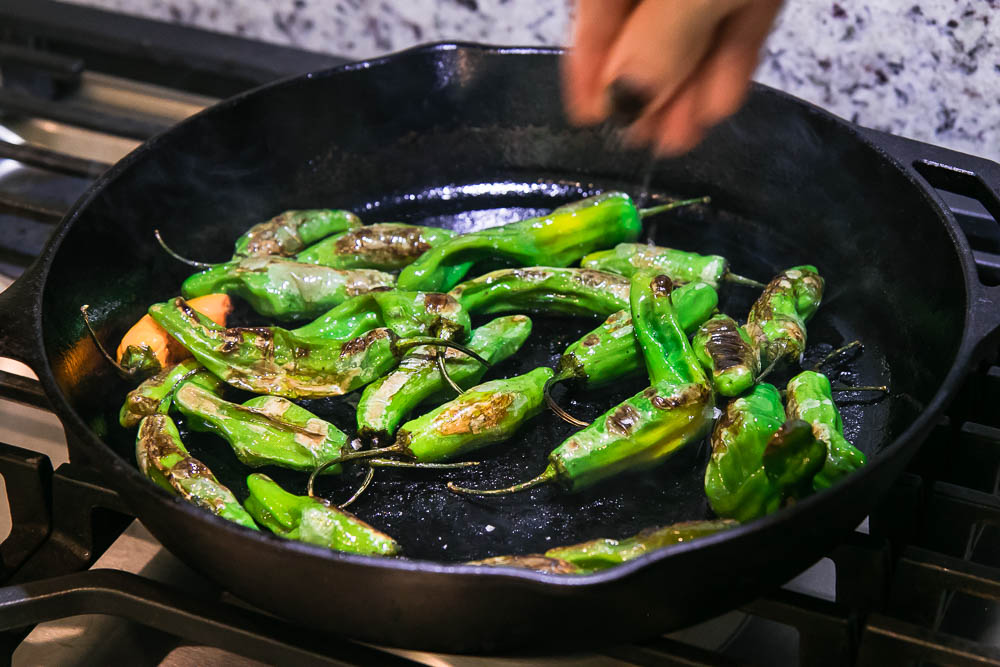 a hand sprinkling salt onto shishito peppers cooking in a cast iron skillet