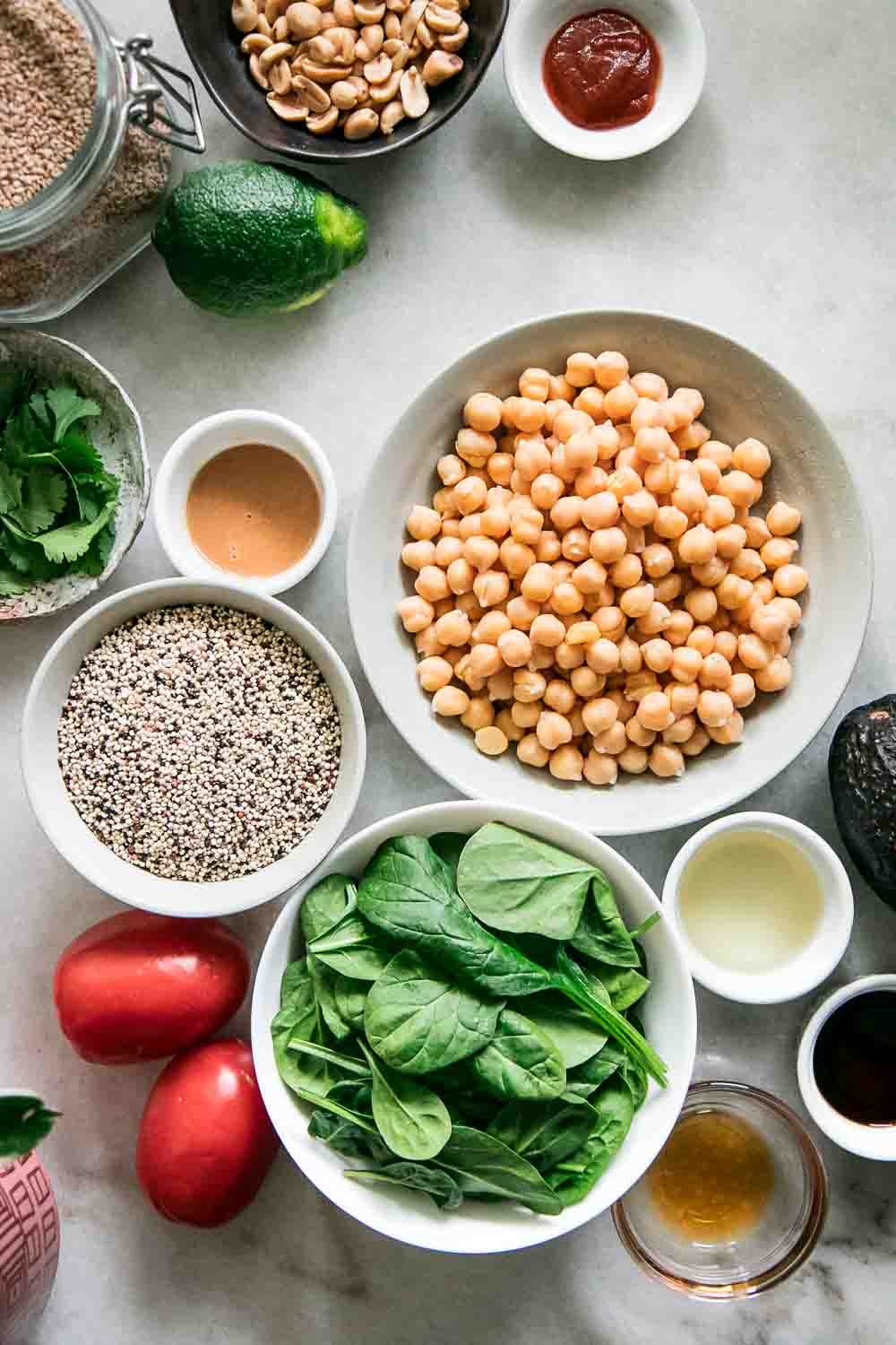 bowls of chickpeas, spinach, quinoa, sesame seeds, and tomatoes on a white table