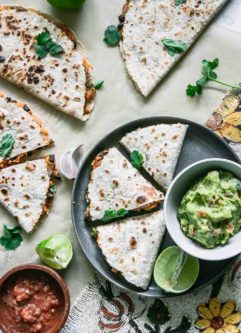 three quesadillas made of sweet potatoes on a plate and a table with a lime and guacamole