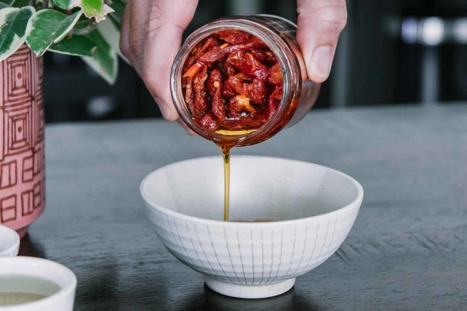 a hand pouring oil from a jar of sun-dried tomatoes into a small white bowl