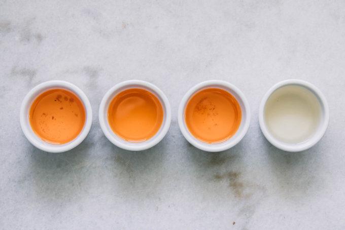 three small ramekins of sun-dried tomato oil and one small ramekin of white wine vinegar on a white countertop