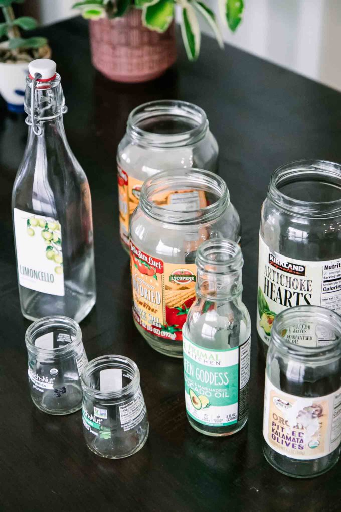 an assortment of empty glass food jars with labels on a wooden table