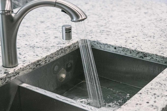 water pouring from a silver faucet into a sink