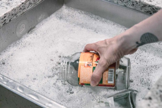 a hand submerging an empty glass food jar with a label into a sink filled with soapy water