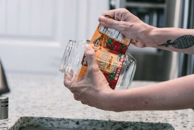 a hand peeling a label from an empty glass food jar