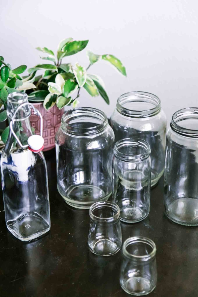 empty glass food jars without labels on a wooden table with a green plant in the background