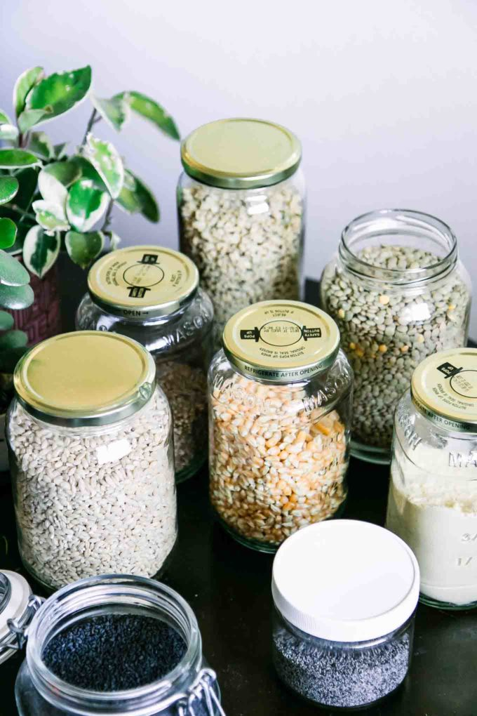 glass food jars filled with dried bulk food on a wooden table with a green plant