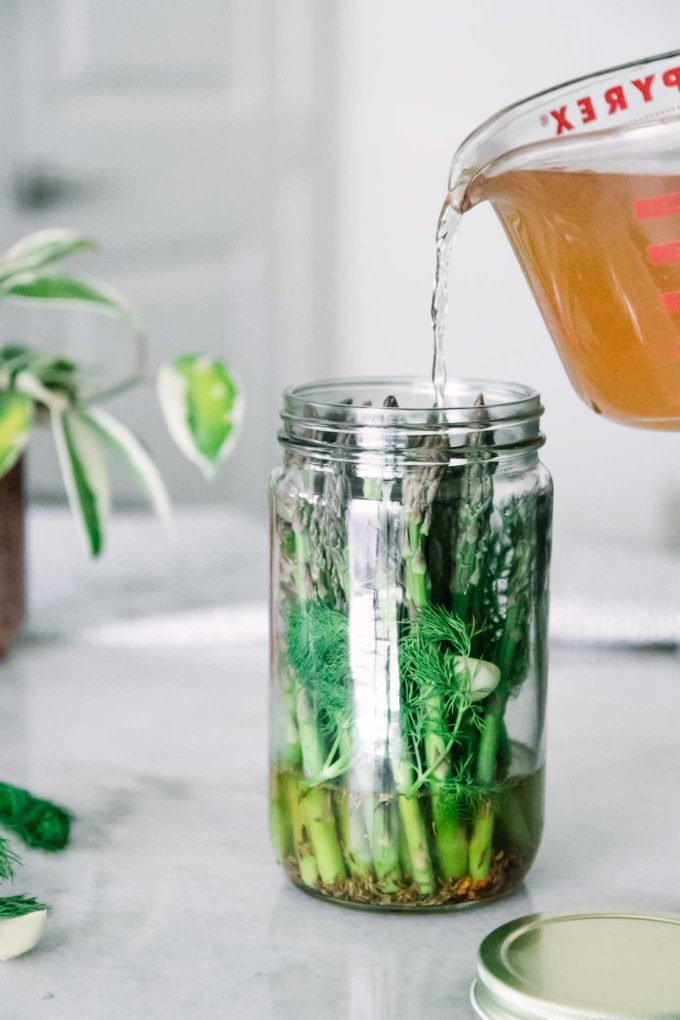 apple cider vinegar brine pouring into a tall glass jar of asparagus with herbs and spices on a white table