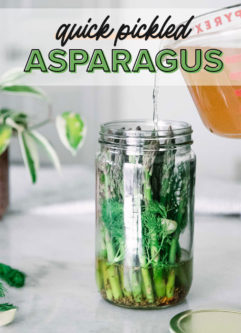 """apple cider vinegar brine pouring into a tall glass jar with asparagus and herbs and the words """"quick pickled asparagus"""" in black and green writing"""