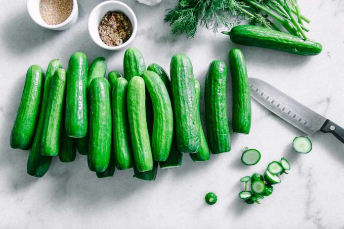 persian cucumbers with stems cut off on a white table