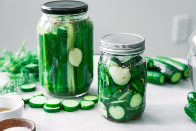 two jars of pickled cucumbers cut into spears and slices on a white table