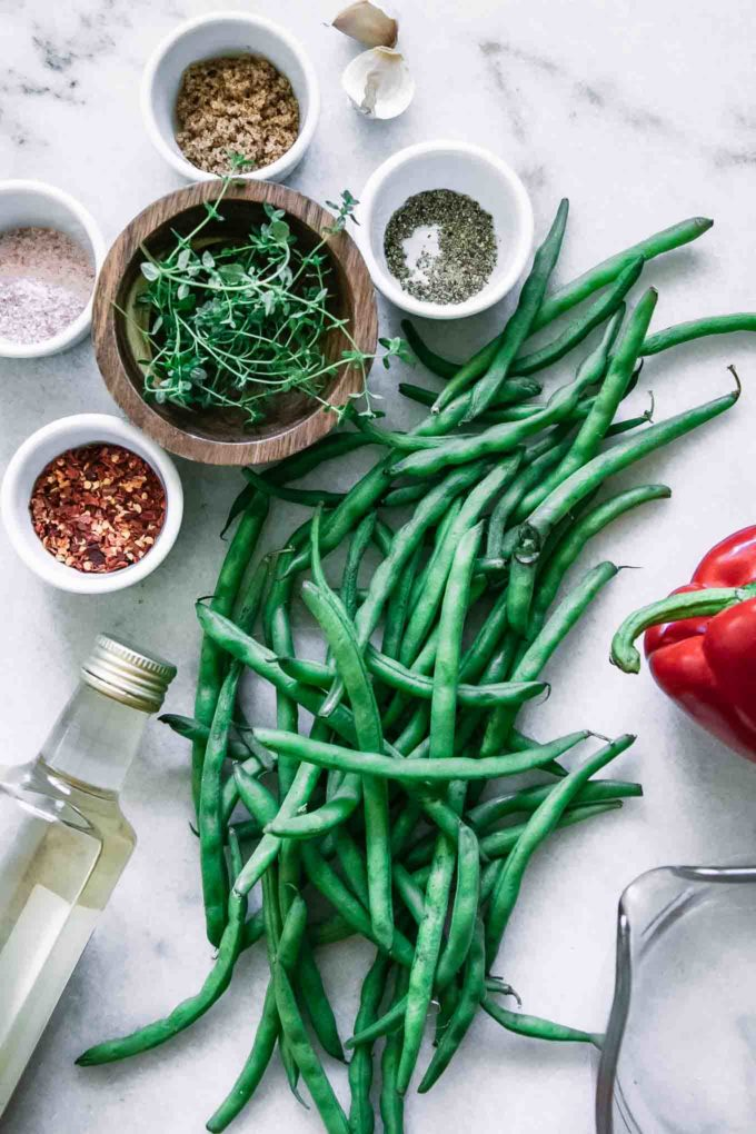 green beans, red bell pepper, garlic, thyme, red pepper, vinegar, water, salt, and sugar on a white countertop