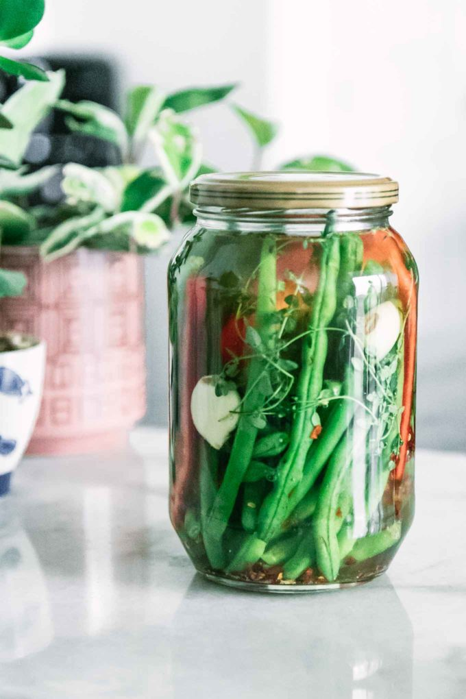 a jar of pickled green beans on a white table