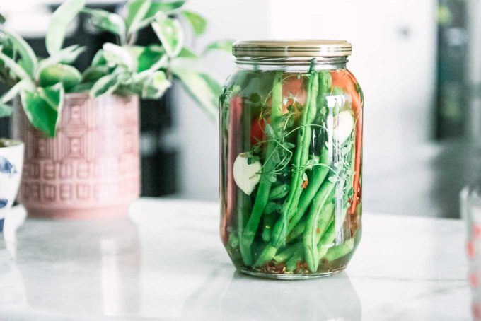 a jar of pickled green beans and bell peppers on a white table with flowers