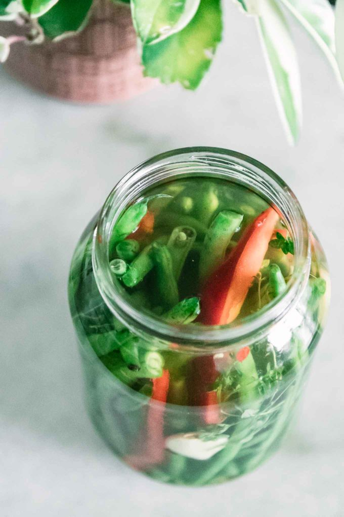 green beans and red bell pepper in a glass jar on a white table