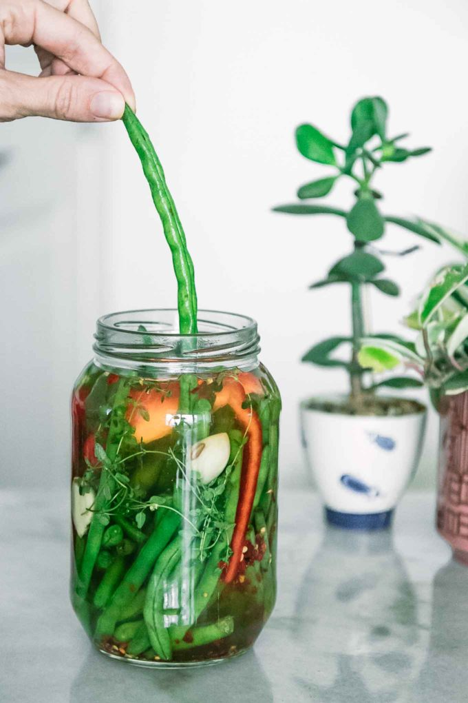 a hand pulling a green bean out of a jar on a white table