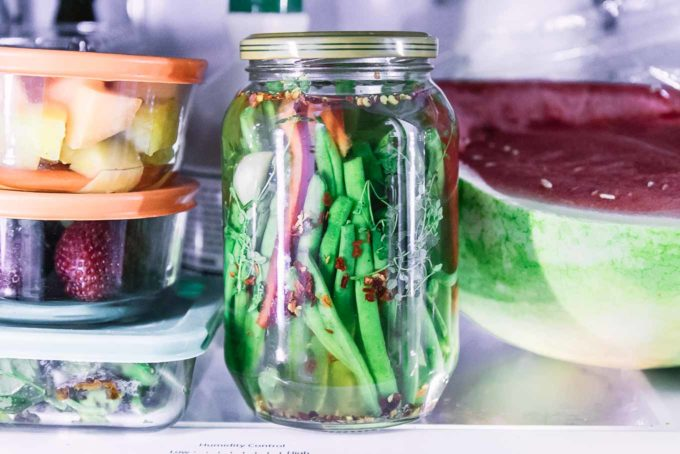 a jar of pickled green beans in a refrigerator
