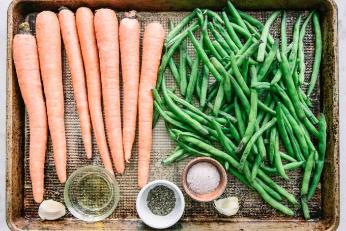 cut carrots, green beans, and garlic and bowls of olive oil, salt, and pepper on a sheet pan