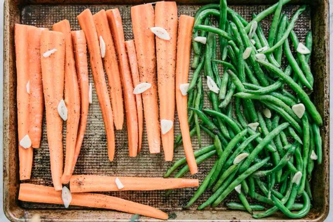 cut carrots and green beans with sliced garlic on a sheet pan