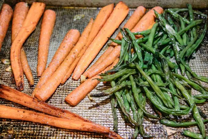 cooked carrots and green beans on a baking sheet