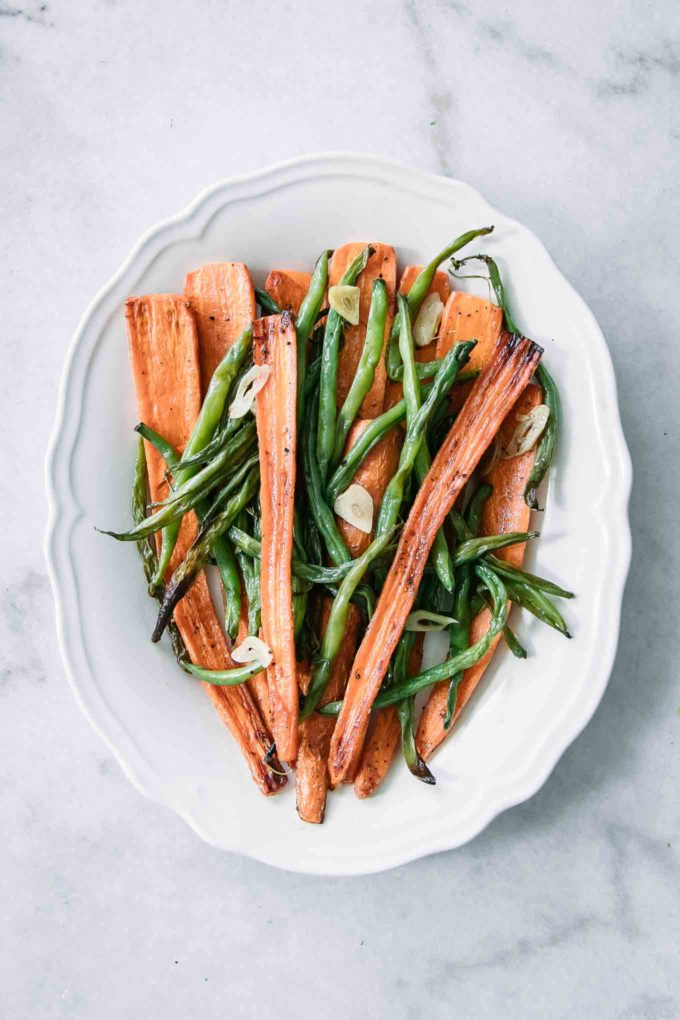 roasted haricots verts and carrots on a white plate