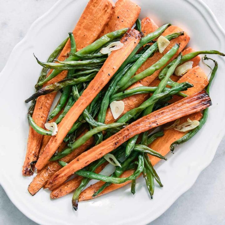 baked green beans, carrots, and garlic in a white serving dish on a white table