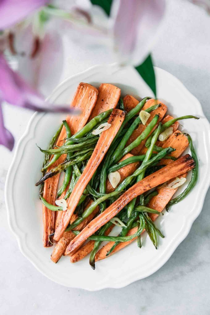 carrots and green beans on a white plate on a white table with a pink flower