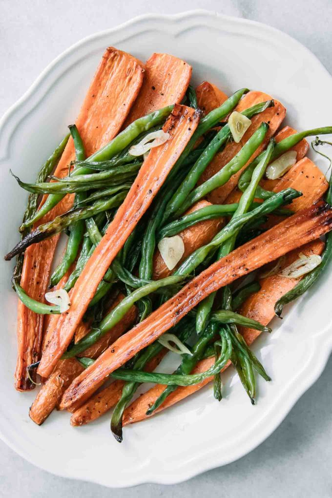 green beans and carrots on a white plate