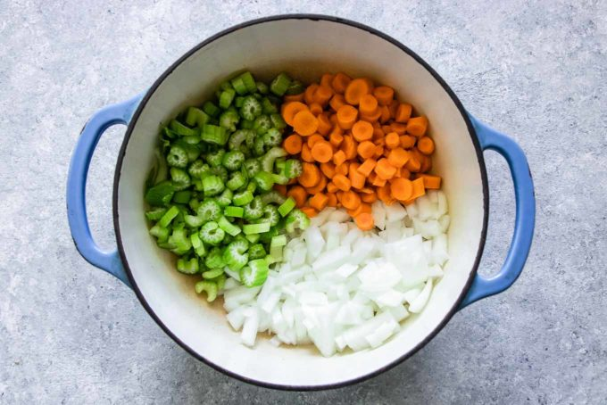 sliced carrots, celery, and onion in a large dutch oven soup pot on a white table