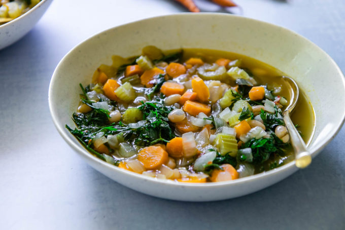 a bowl of carrot greens soup on a blue table with a gold spoon