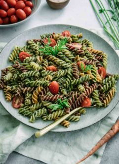 pesto pasta with cherry tomatoes on a blue plate with a gold fork