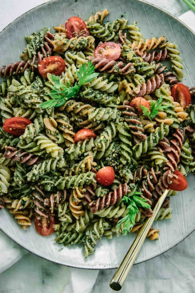 a close up photo of rotini pasta with pesto sauces and sliced red cherry tomatoes