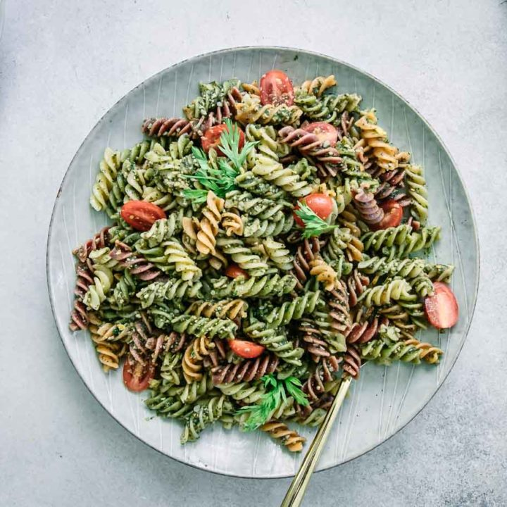 pesto pasta with cherry tomatoes on a white plate on a white table with carrots and a bowl of tomatoes
