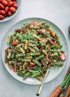 rotini pasta with carrot top pesto sauce on a blue plate with a gold fork