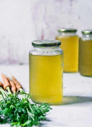a glass jar of vegetable broth made from carrot tops on a white table with carrots with green leaves in the foreground