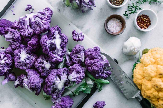 cut purple cauliflower on a cutting board with a knife