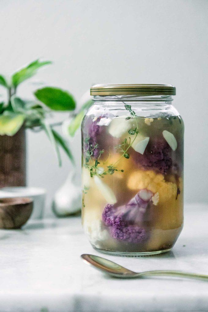 a jar of rainbow cauliflower in a pickling brine on a white table