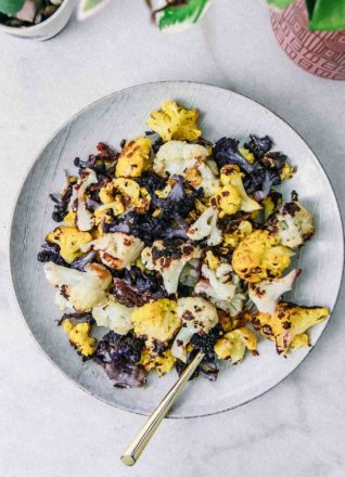 roasted white, purple, and orange cauliflower on a white plate with a gold spoon