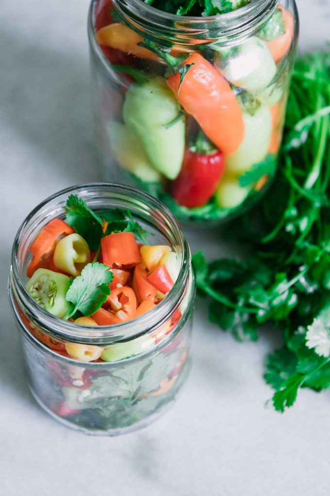 sliced and whole peppers in glass jars with fresh herbs and spices before pickling