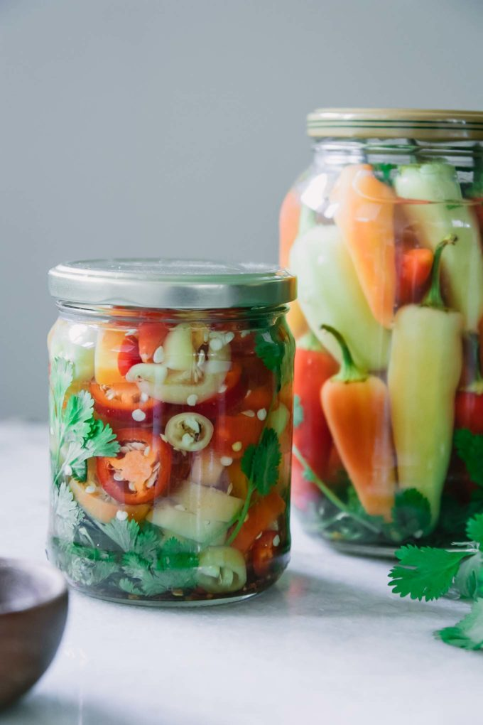a jar of sliced pickled peppers on a white table