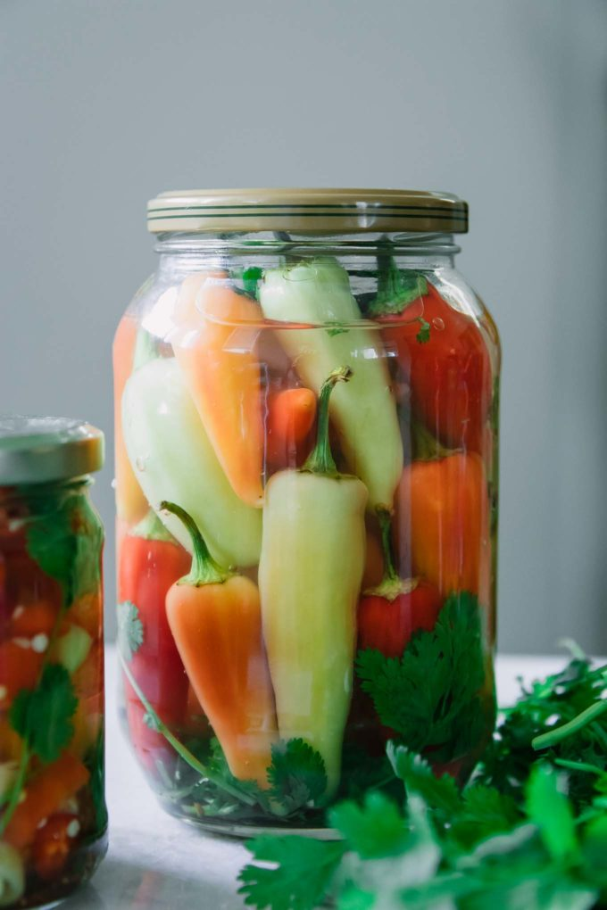 a jar of whole pickled peppers on a white table