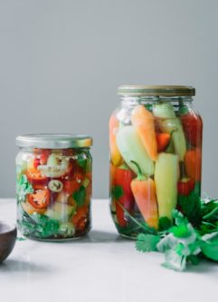 two jars of pickled peppers, one with sliced peppers and one with whole peppers