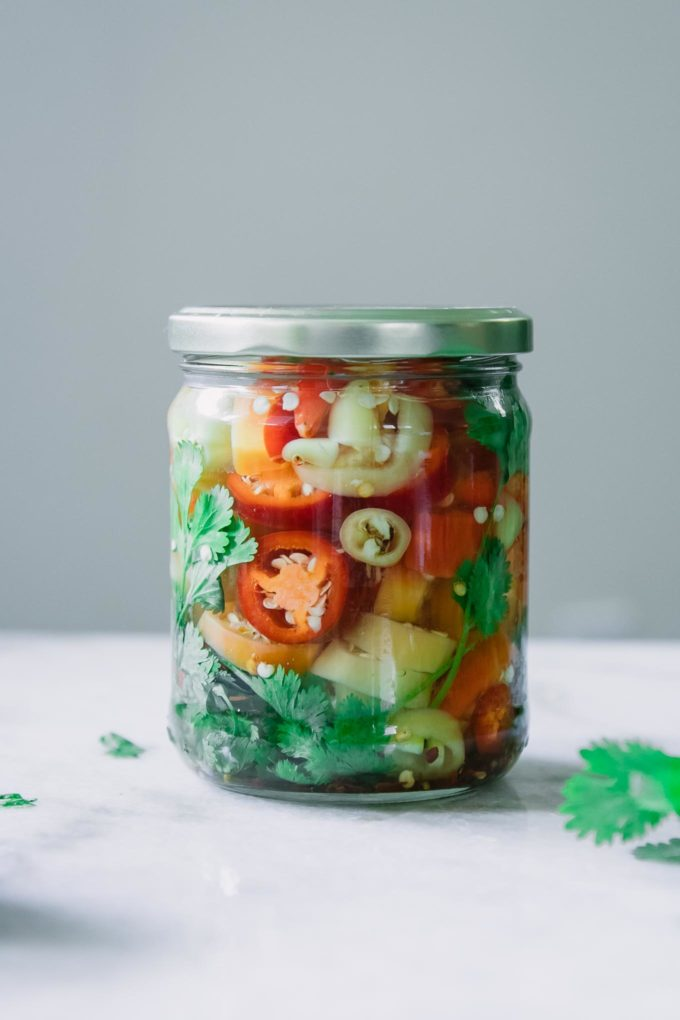 a jar of sliced pickled red, orange, and yellow peppers on a white table