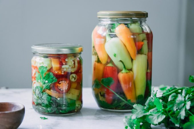 two jars of pickled peppers on a white table with fresh cilantro