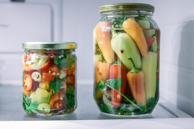 two jars of sliced and whole pickled peppers on a refrigerator shelf