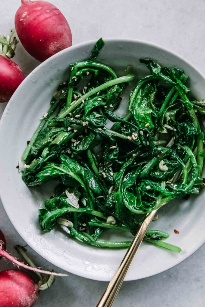 sauteed radish greens in a white bowl with a gold fork