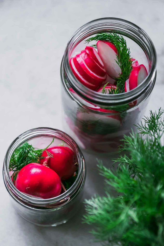 sliced and whole radishes in glass jars with fresh dill