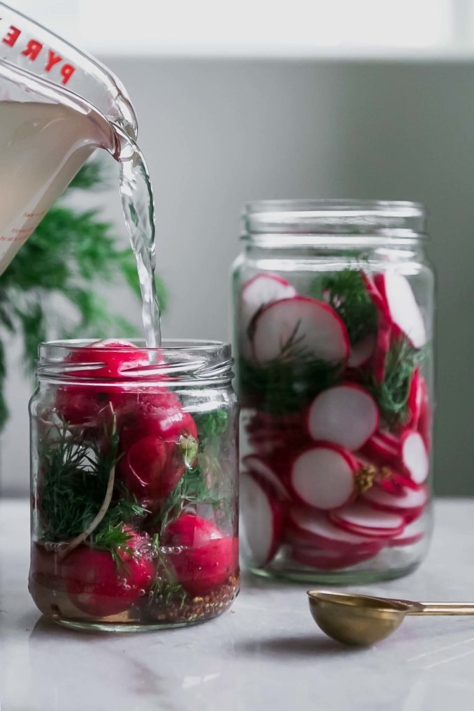 vinegar pickling brine pouring into a jar of radishes