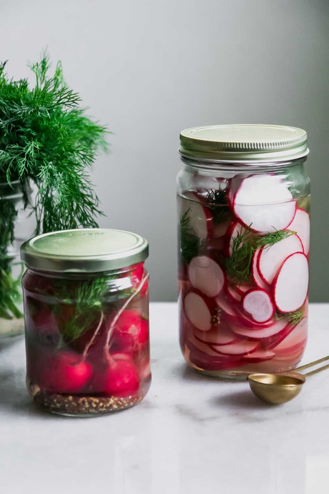 two jars of sliced and whole pickled radishes on a white table with fresh dill