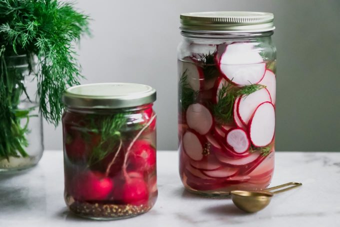 two jars of sliced and whole pickled radishes on a white table